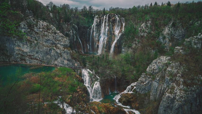 4k UHD Cinemagraph of fresh blue water flowing down beautiful waterfalls between a wooden foot bridge in the famous Plitvice National Park in Croatia, where the classic Winnetouies were filmed. | Shutterstock HD Video #1037886944