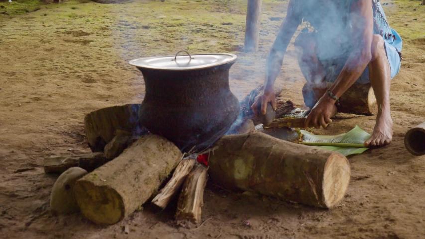 amazonian indigenous chief crushing ayahuasca sticks in ecuador
