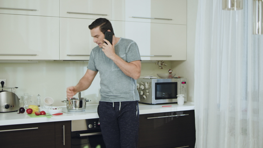 Angry man talking phone at kitchen. Frustrated businessman having unpleasant conversation at luxury kitchen. Aggressive man swinging arms during phone talk at home. | Shutterstock HD Video #1037900501