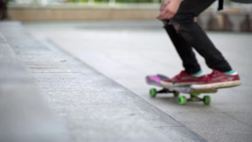 A guy on a bright, colored skateboard, tries to harness onto a concrete staircase and falls.Blurred focus.