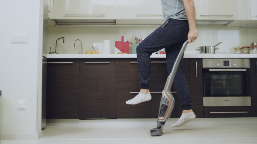 Happy man cleaning floor at kitchen. Man legs jumping around apartment with cleaner machine in slow motion. Joyful guy having fun with vacuum cleaner at home. #1037908781