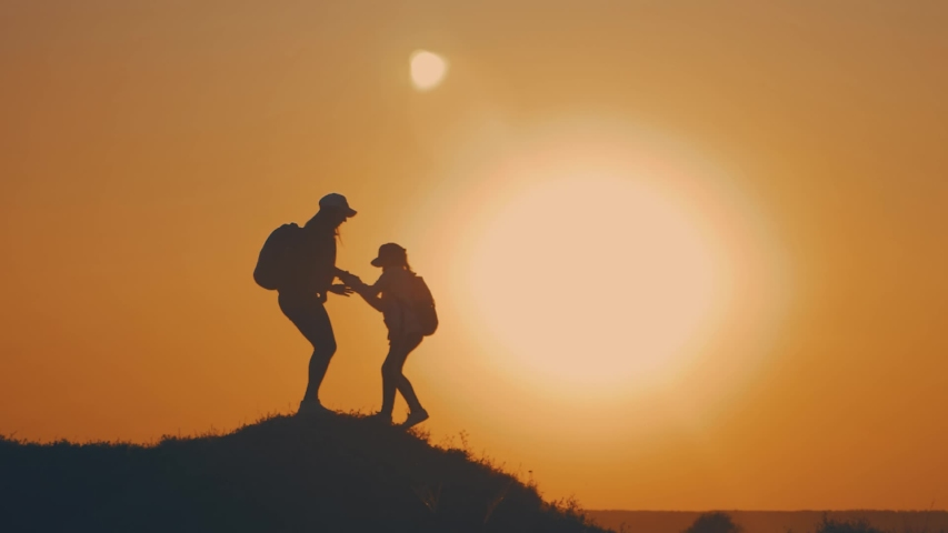 Girl helps her friend climb up the last section of mountain. Tourists with backpacks help each other, silhouette with sunset. The joint work teamwork. Tourism, travel and healthy lifestyle concept. | Shutterstock HD Video #1037911283