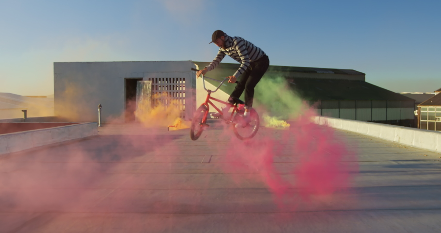 Rear view of a young Caucasian man riding a BMX bike and doing tricks on the rooftop of an abandoned warehouse, with a pink smoke grenade attached to the bike  in slow motion