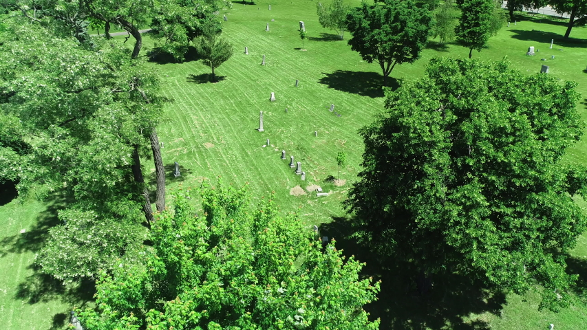 Drone aerial of cemetery with gravestones, graves and trees. Themes of death, peace, sadness, renewal.  | Shutterstock HD Video #1037950448