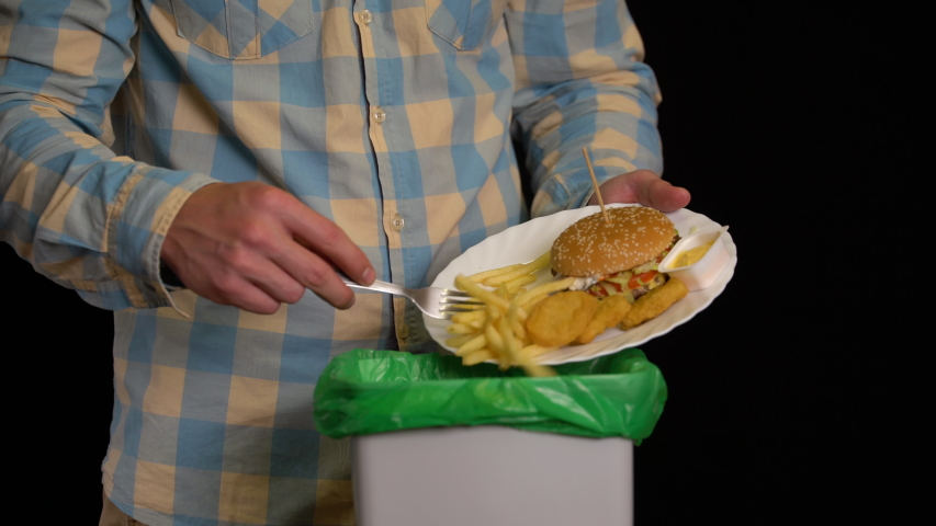 Man scraping with a plate a burger, french fries, nuggets, cheese sauce into garbage bin. | Shutterstock HD Video #1037950958