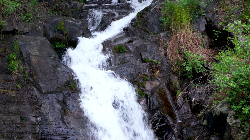 A cascade of water falling from a height running down the cliff. Green vegetation grows along the steep rocky slope #1037952023