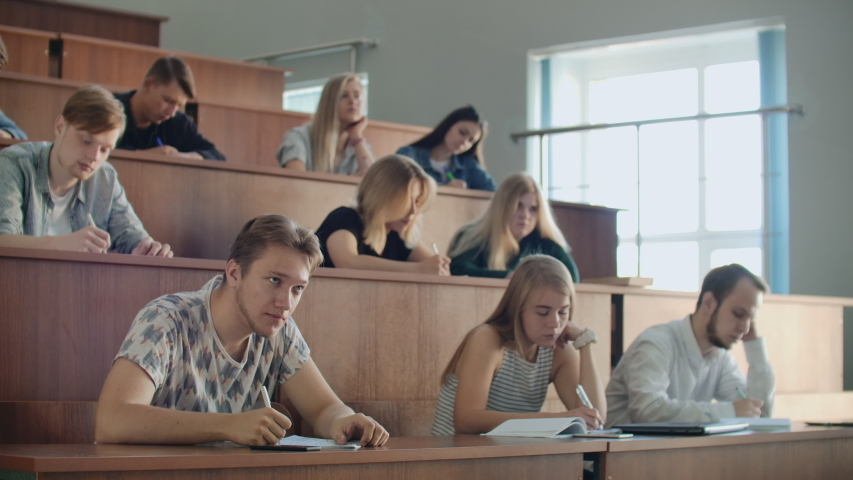 A group of students in the audience listens to the teacher and writes a lecture summary Royalty-Free Stock Footage #1037955644