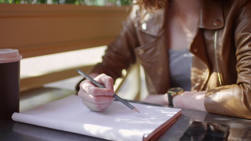 Tilt up shot of beautiful teenage girl with freckles and red hair sitting at table on summer terrace of cafe and sketching in notebook, then drinking coffee and looking away from camera | Shutterstock HD Video #1037966921