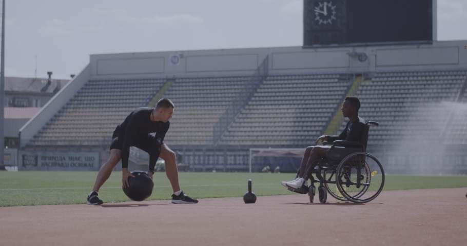 Full shot of a wheelchaired athlete and his trainer working out with a medicine ball