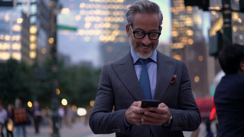 Slow motion of smiling mature lawyer in expensive suit messaging with customers via cellular device while walking in financial district,successful businessman in optical eyewear searching trading news Royalty-Free Stock Footage #1037982434