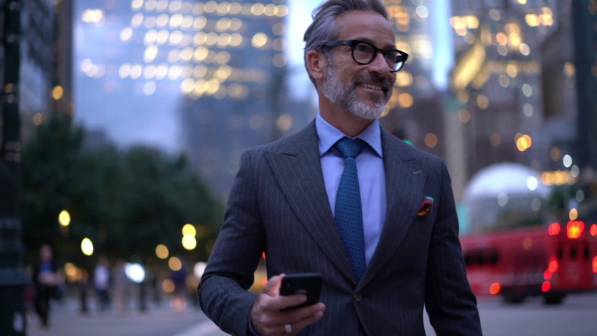 Middle aged businessman in luxury clothing using mobile phone for texting during way to office in financial district in metropolitan city, successful male proud ceo smiling during cellular messaging