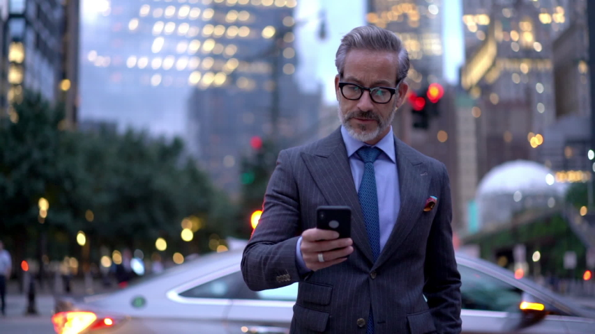 Mature male employer formally dressed walking in metropolitan downtown and typing text message for send via smartphone device, middle aged businessman using mobile device for phoning outdoors  | Shutterstock HD Video #1037983112