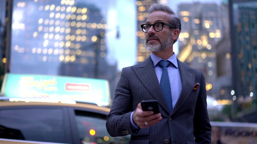 Slow motion effect of successful male entrepreneur dialing number on modern cellphone device while standing at metropolitan street with transport traffic on background, mature businessman using mobile | Shutterstock HD Video #1037983448