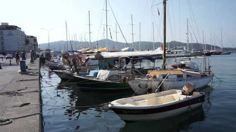 Turkey, Fethiye - August 2019. Fishing boats and yachts moored to the pier on the promenade of the city. Tourists and visitors walk along promenade and explore the sights. Travel to Turkey. Sea bay.