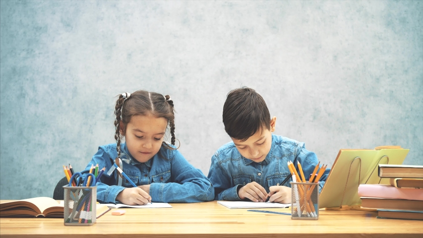 Schoolkids, brother and sister, sitting at the table, writing, pointing their thumbs up, smiling at the camera. | Shutterstock HD Video #1037993705