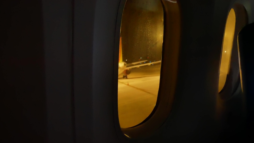 video from inside the plane through the windows of aircraft while taxiing on taxi way in the evening flight time #1037998118