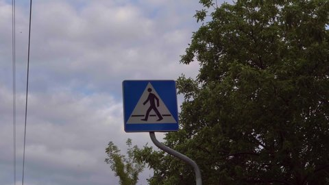 sign pedestrian crossing with trees and sky in the background