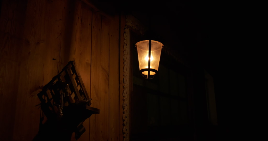 Iron lantern swaying in wind, night light, shadows on wooden wall of rustic barn. lonely lantern on dark street, wind sways, shadows run along wooden wall, ominous atmosphere, warm light of lantern