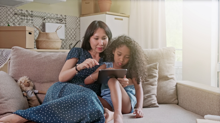 Mother and Daughter having fun on a digital tablet in a home interior. A cute happy mother and daughter using a digital tablet at home in the living room. #1038037772