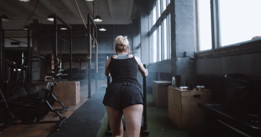 Willpower and motivation, camera follows young athletic woman pushing heavy training sled training in gym slow motion.   Shutterstock HD Video #1038039905