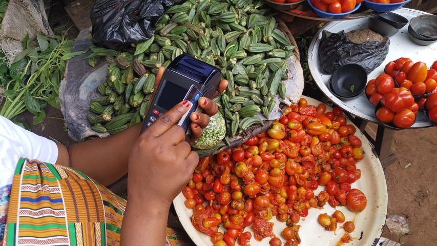 african woman in a local market using a pos machine to process payment from a customer before handing the customer the items bought Royalty-Free Stock Footage #1038049229