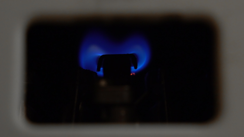 Gas water heater ignited by a wick. Blue fire close up