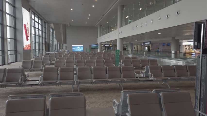 Many seats at empty airport terminal waiting area. No people in lounge at evacuated airport. Low season means poor business for air travel. Airport abandoned after terrorist attack.
