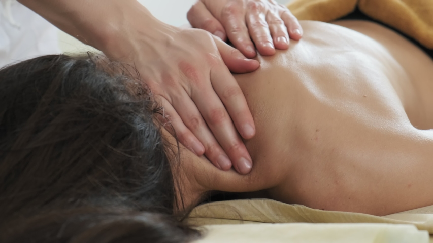 Young woman having massage in spa salon. Close-up of woman relaxing during back massage lying on massage table in slow motion