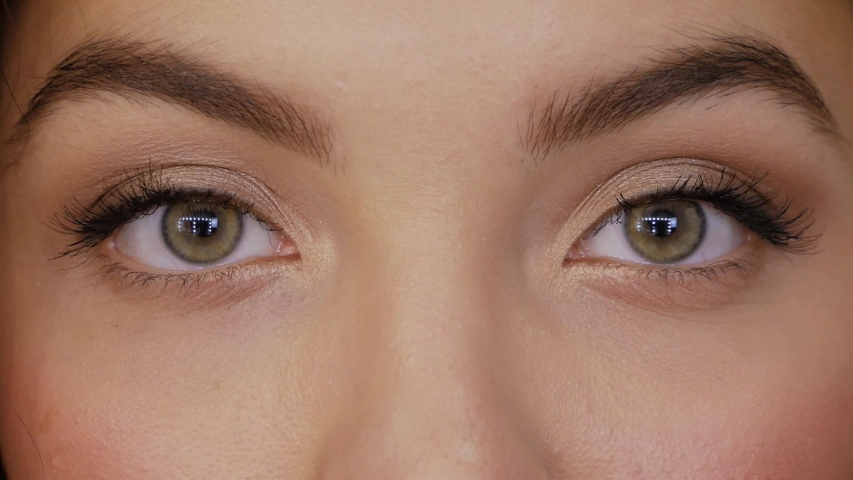 Young woman looks straight into the frame and closes her eyes slow motion. Beautiful girl with green brown eyes close-up | Shutterstock HD Video #1038080945