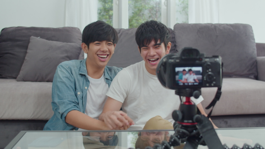 Young Asian gay couple influencer couple vlog at home. Teen korean LGBTQ men happy relax fun using camera record vlog video upload in social media while lying sofa in living room at house concept. | Shutterstock HD Video #1038087137