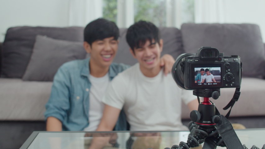 Young Asian gay couple influencer couple vlog at home. Teen korean LGBTQ men happy relax fun using camera record vlog video upload in social media while lying sofa in living room at house. Slow motion | Shutterstock HD Video #1038087152