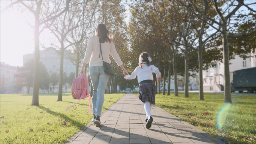Young woman and little girl in school uniform are holding hands and running along the trees in the park at sunny autumn weather. Family late for school concept, steadicam shot back view. Royalty-Free Stock Footage #1038087674