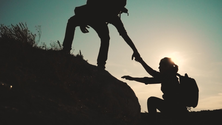 Teamwork help business travel silhouette slow motion video concept. Helping hand silhouette between two climbers. teamwork group of tourists lends a helping hand climb the cliffs mountains. couple man