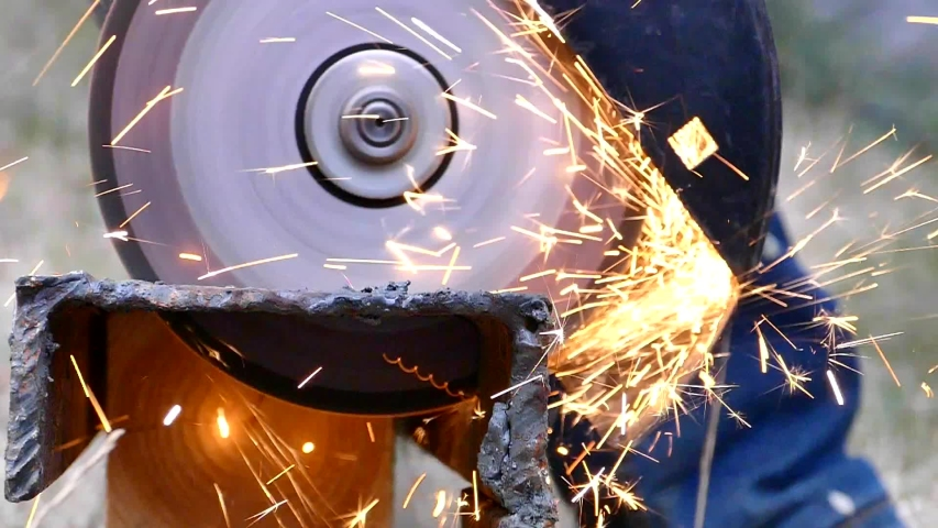 Metal cutting with a cutting wheel of an angle grinder. Sparks fly from the grinder. Worker builds a metal structure. Close-up. | Shutterstock HD Video #1038093491