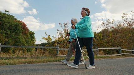Elderly senior women practicing Nordic walking outdoors, healthy lifestyles in old age. Slow-motion 4k video