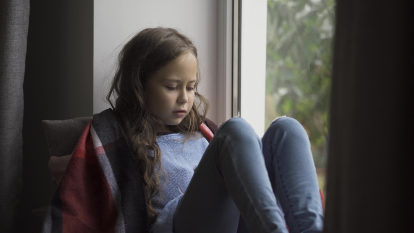 Sick caucasian girl covered in blanket sitting on windowsill at home. The child has fever, she is cold. Concept of health, illness, sickness, cold, treatment | Shutterstock HD Video #1038103088