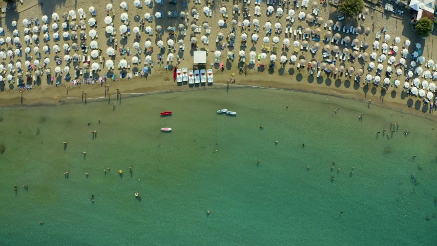 Aerial view of the beach filled with people on a hot sunny day. Sun umbrellas stand in yellow bright sand. People rest and sunbathe on the beach on a summer day near the sea. Rhodes Lindos Greece | Shutterstock HD Video #1038104918