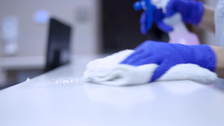 Janitor cleaning medical counter in office with commercial sanitizing cleaner with blue surgical gloves with shallow depth of field