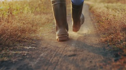 Close-up of a farmer's feet in rubber boots walking down a country road between fields, dust rising from shoes. Slow-motion 4k video