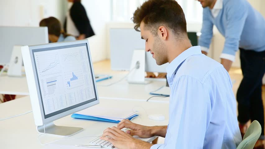 Young businessman sitting in front of desktop | Shutterstock HD Video #10381283