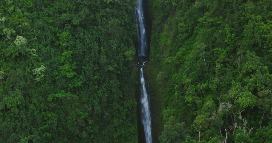 Aerial shot flying up two pristine waterfalls surrounded by lush green jungle foliage #1038128348