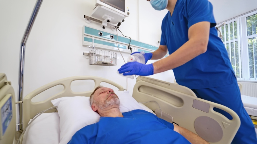 Professional doctor in medical uniform gives resuscitation to a male patient in the emergency room. Man is lying in bed without signs of life. Medical care. Royalty-Free Stock Footage #1038132266