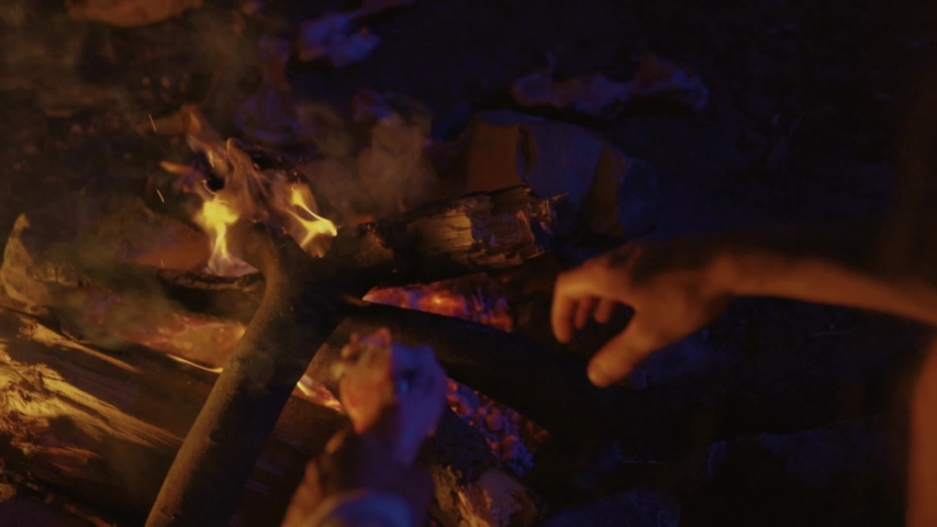 Close-up stone-age neanderthal hands warming up on fire. Prehistoric human ancestor in cavern making bonfire at night.