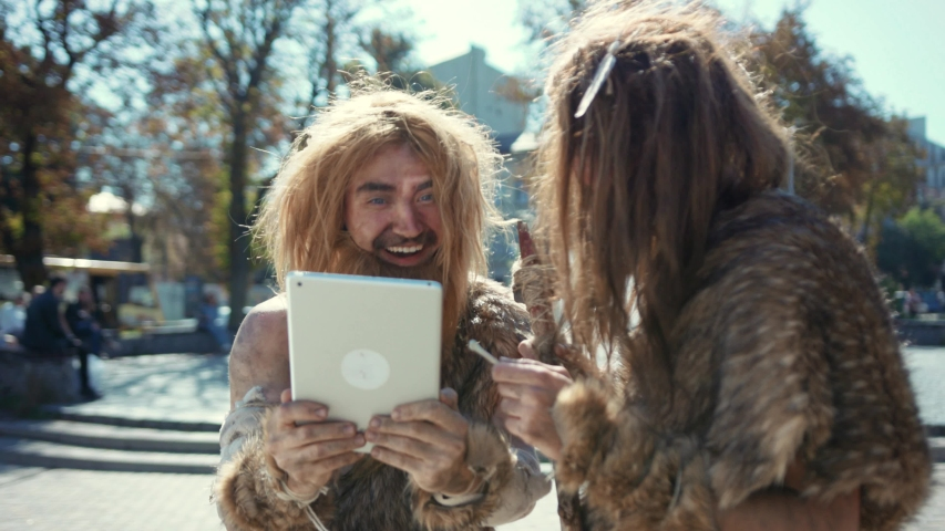 Happy savages in animal fur using modern tablet browsing internet having fun. Hunter-gatherers of ancient tribe in modern times. Evolution.