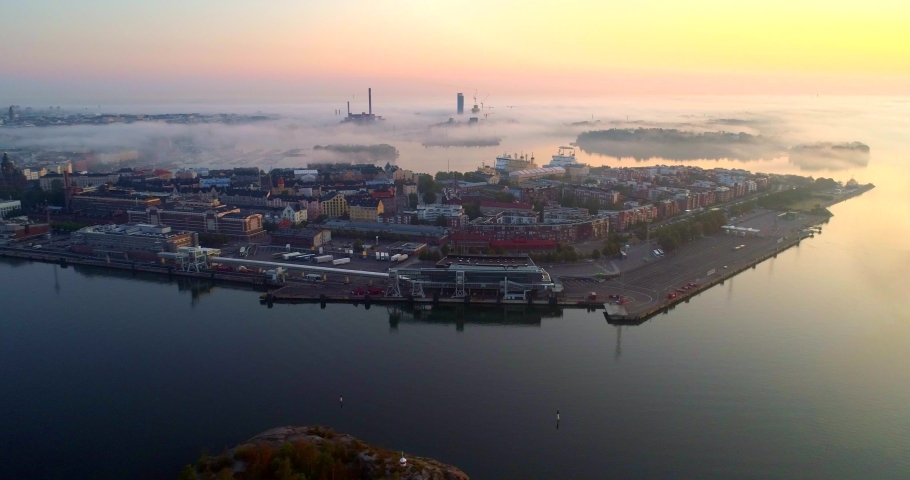 Helsinki foggy morning, Aerial, tracking, drone shot, katajanokka cityscape, colorful sky and fog clouds, over the tervasaari island and the sea, at sunrise, on a sunny and misty autumn dawn, in