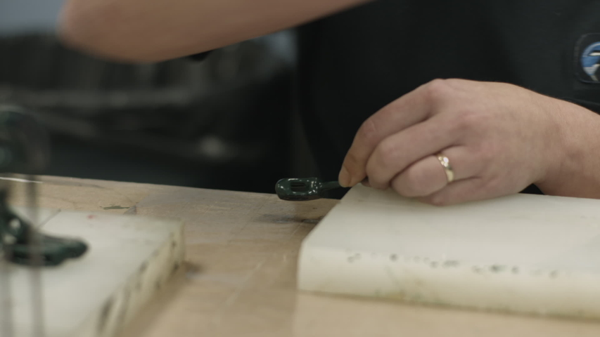 Factory worker applies rubberized coating to metal parts by hand slider shot hands only | Shutterstock HD Video #1038175364