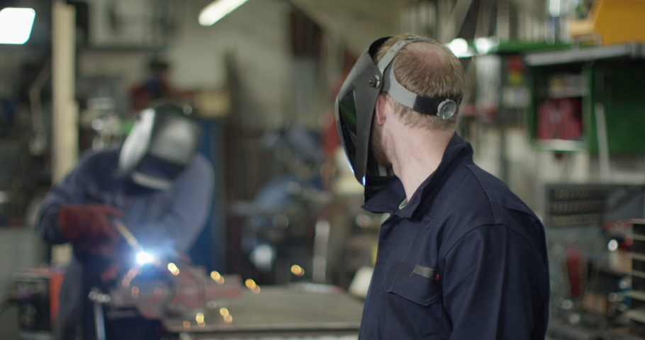 4K Mechanic in garage workshop lifting his welding visor & looking at camera. Slow motion. Royalty-Free Stock Footage #1038194096