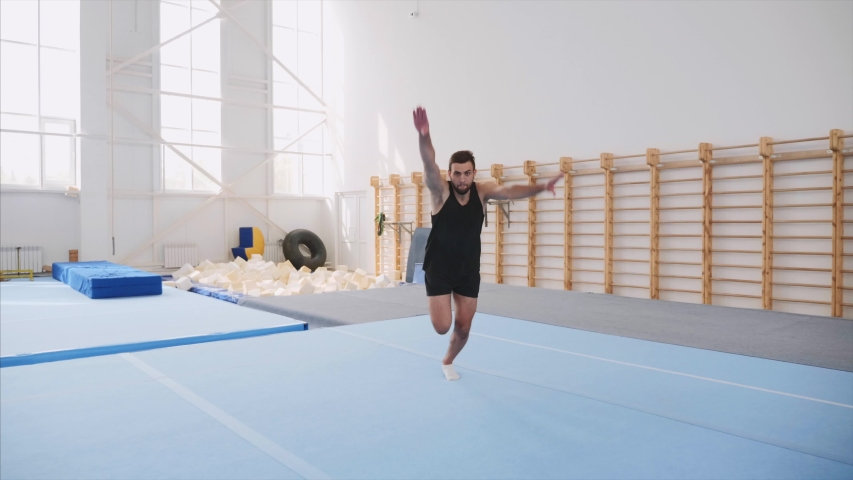 A male athlete is making four back flips at once in front of the camera and lands on feet in the gym in black shorts and T-shirt, sport equipment at the background, steadicam, front view, slow motion.