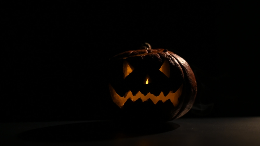 Halloween, orange pumpkin with a scary glowing face in the dark. Thick gray smoke comes out and spreads on the black table. A close-up of a flickering flashlight on the eve of all the saints. | Shutterstock HD Video #1038206426