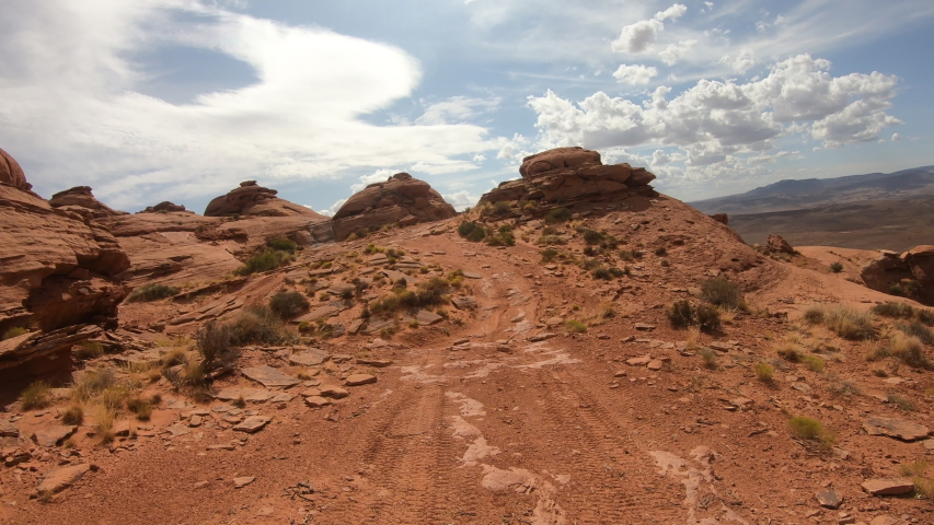 Extreme desert rocks off road recreation climbing POV. Geologic landscape in southern Utah. Erosion sandstone rocks, cliffs, sand dunes, deep canyons.  Dangerous wilderness desert environment.   Shutterstock HD Video #1038217628